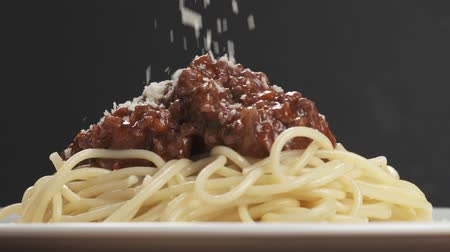spagetti : Slow motion close-up strooi spaghetti bolognese met geraspte oude parmezaanse kaas Stockvideo