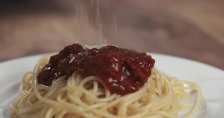 spagetti : Slow motion closeup sprinkle spaghetti bolognese with grated aged parmesan cheese