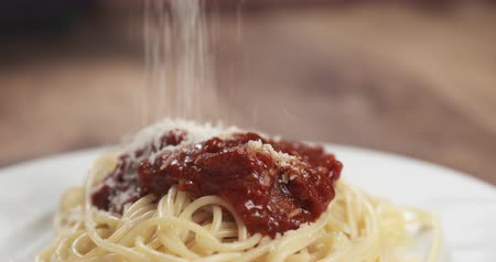 İtalyan : Slow motion closeup sprinkle spaghetti bolognese with grated aged parmesan cheese