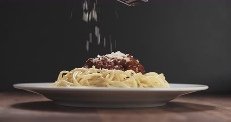 spagetti : Slow motion sprinkle grated aged parmesan cheese over spaghetti bolognese