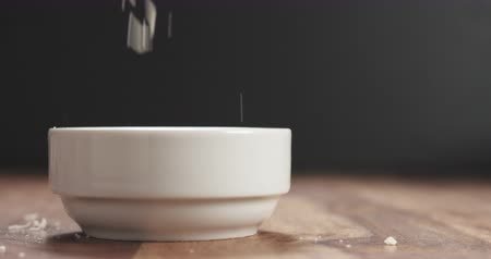 parmigiano : Slow motion closeup of grating aged parmesan in white bowl on wood table Stock Footage