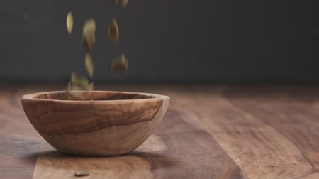 peeled grains : Slow motion pumpkin seeds falling in wood bowl with copy space