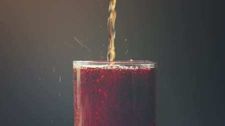 kola : cola pouring into the glass over dark background with splashes and bubbles in slow motion