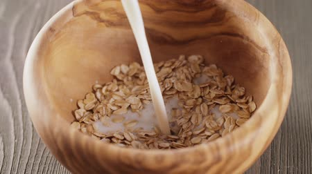 yulaf ezmesi : oat flakes milk pour wood olive bowl closeup slow motion footage