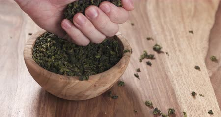 folhas : Slow motion man hand check dried tea leaves in bowl on table