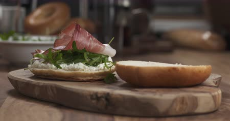 вылеченный : Slow motion man hands put prosciutto on bagel on wood board