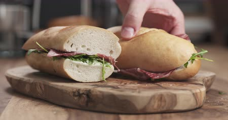 вылеченный : Slow motion man hands take baguette sandwich with coppa from wood board Стоковые видеозаписи