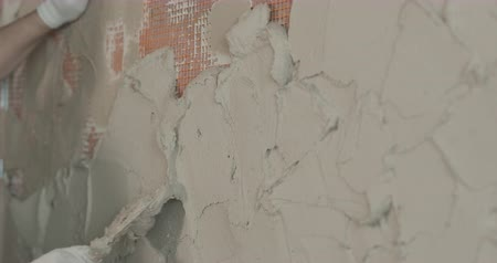 миномет : Slow motion handheld shot of worker applying plaster on the wall