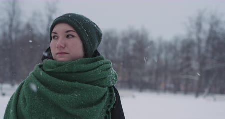 um : Slow motion portrait of teen girl walking in park on a winter day
