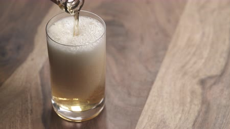 quartilho : closeup pour ginger beer in a glass on wood table