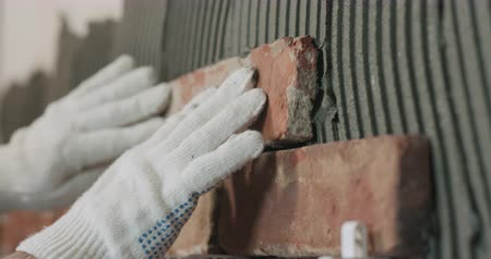 cserepezés : closeup worker applying brick cuts tile to the wall