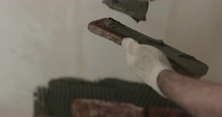 cserepezés : Slow motion closeup worker applying concrete glue to brick tile