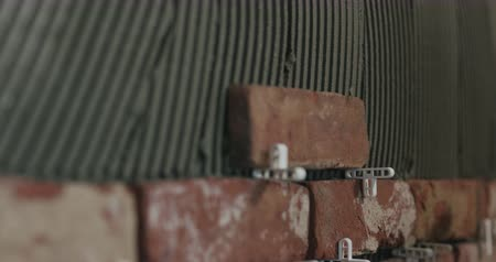мастер на все руки : Slow motion pan closeup worker applying brick cuts tile to the wall