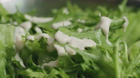 salad : Slow motion closeup pouring caesar sauce on frillis salad leaves