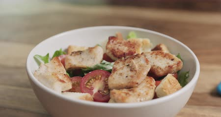 свежий : Slow motion closeup adding chicken to caesar salad