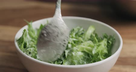 close up : Slow motion frillis salad leaves falling into white bowl