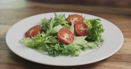 tomates cereja : Slow motion closeup adding tomatoes to caesar salad