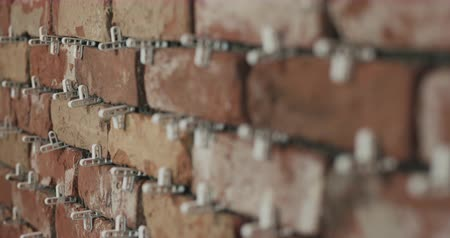 cserepezés : Slow motion focus pull of brick cuts tile on the wall