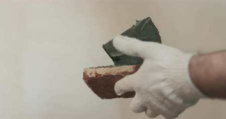 cserepezés : Slow motion closeup pan of worker applying concrete glue to brick tile