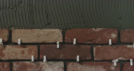 cserepezés : Slow motion pan of brick cuts tile on the wall Stock mozgókép