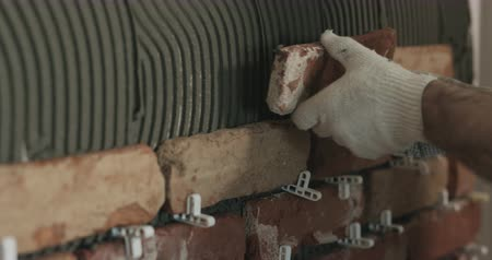 cserepezés : Slow motion closeup worker applying brick cuts tile to the wall
