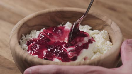 twaróg : Slow motion closeup mixing cowberry jam with cottage cheese in wood bowl