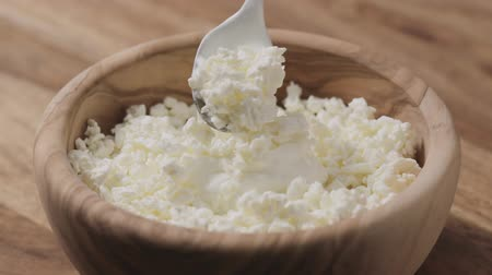 coalhada : Slow motion closeup mixing sour cream with cottage cheese in wood bowl
