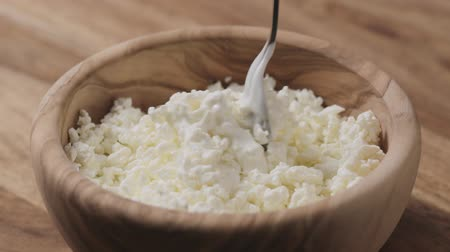 cálcio : Slow motion closeup mixing sour cream with cottage cheese in wood bowl