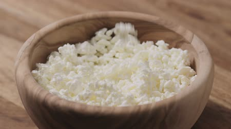 tvaroh : Slow motion closeup cottage cheese falling into wood bowl Dostupné videozáznamy