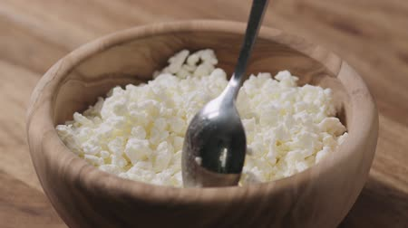 cálcio : Slow motion closeup crumbly cottage cheese in wood bowl