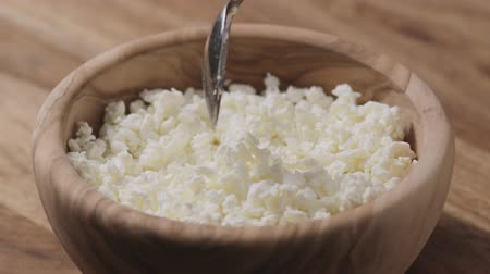 coalhada : Slow motion closeup crumbly cottage cheese in wood bowl
