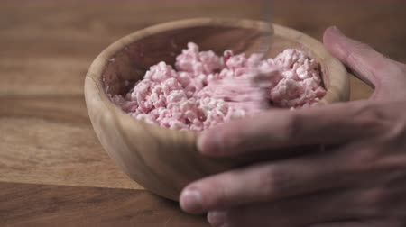 tvaroh : closeup mixing cowberry jam with cottage cheese in wood bowl