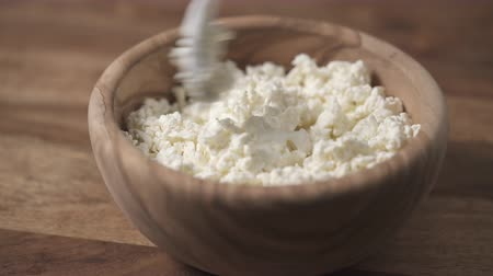 queijo : closeup sour cream pour on cottage cheese in wood bowl