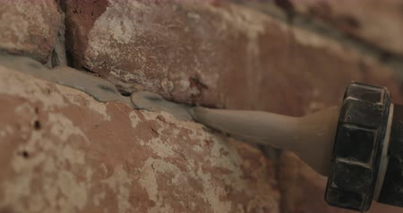 tijolos : Slow motion handheld closeup of worker filling seam between bricks with mortar from sealant gun