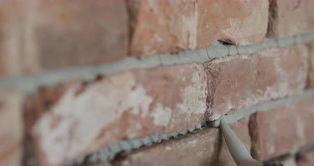 pedreiro : Slow motion pan closeup of worker filling seam between bricks with mortar from sealant gun Vídeos
