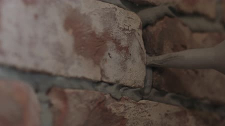 zedník : Slow motion handheld closeup of worker filling seam between bricks with mortar from sealant gun