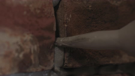 pedreiro : Slow motion handheld closeup of worker filling seam between bricks with mortar from sealant gun