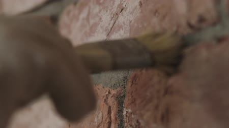 zedník : Slow motion handheld closeup of worker cleaning seam between bricks with brush Dostupné videozáznamy