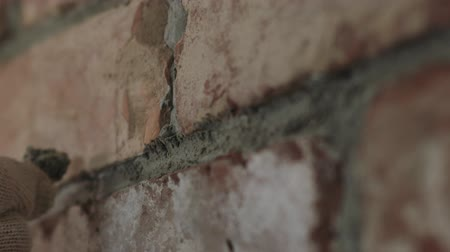 миномет : Slow motion handheld closeup of worker forming seam between bricks Стоковые видеозаписи