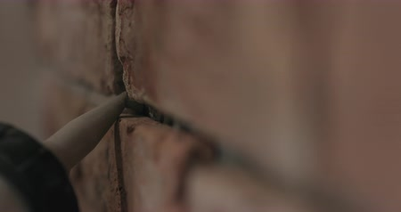 csempe : Slow motion handheld closeup of worker filling seam between bricks with mortar from sealant gun