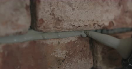 processo : Slow motion handheld closeup of worker filling seam between bricks with mortar from sealant gun