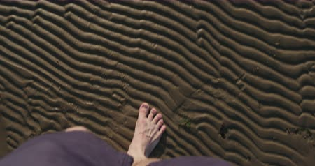 bare foot : Slow motion pov view man walking barefoot in shallow water on beach