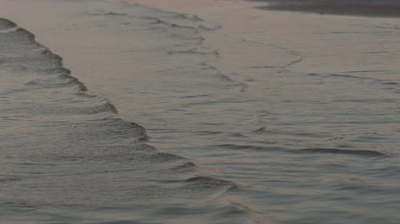 kék háttér : Slow motion handheld closeup of small waves on a beach at sunset Stock mozgókép