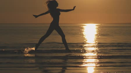 sekély : Slow motion silhouette teenage girl running in shallow water on a beach