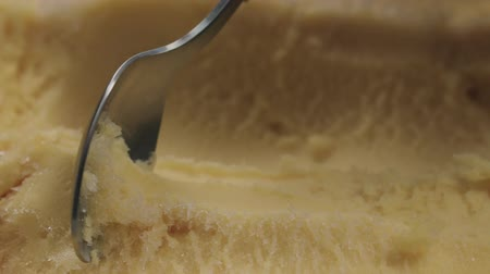 fattening : Slow motion closeup scooping with tea spoon orange sorbet Stock Footage