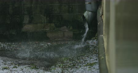 bica : Slow motion of water stream from pipe during strong rain with hailstorm