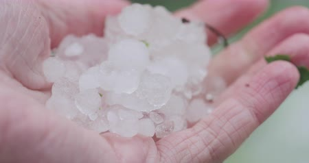 fenomen : Slow motion closeup pov male hand holding hailstones after hailstorm
