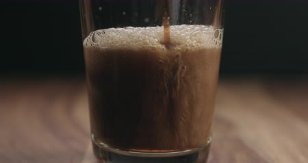 bares : Slow motion closeup pan of beer pour into a glass on wooden table Vídeos