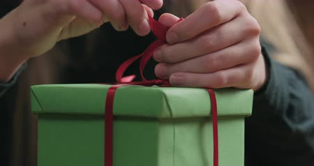 луки : Slow motion closeup of young female hands making red ribbon bow on green paper gift box Стоковые видеозаписи