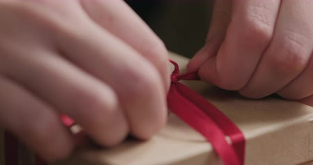 луки : Slow motion macro shot of young female hands opens craft paper gift box with red ribbon bow